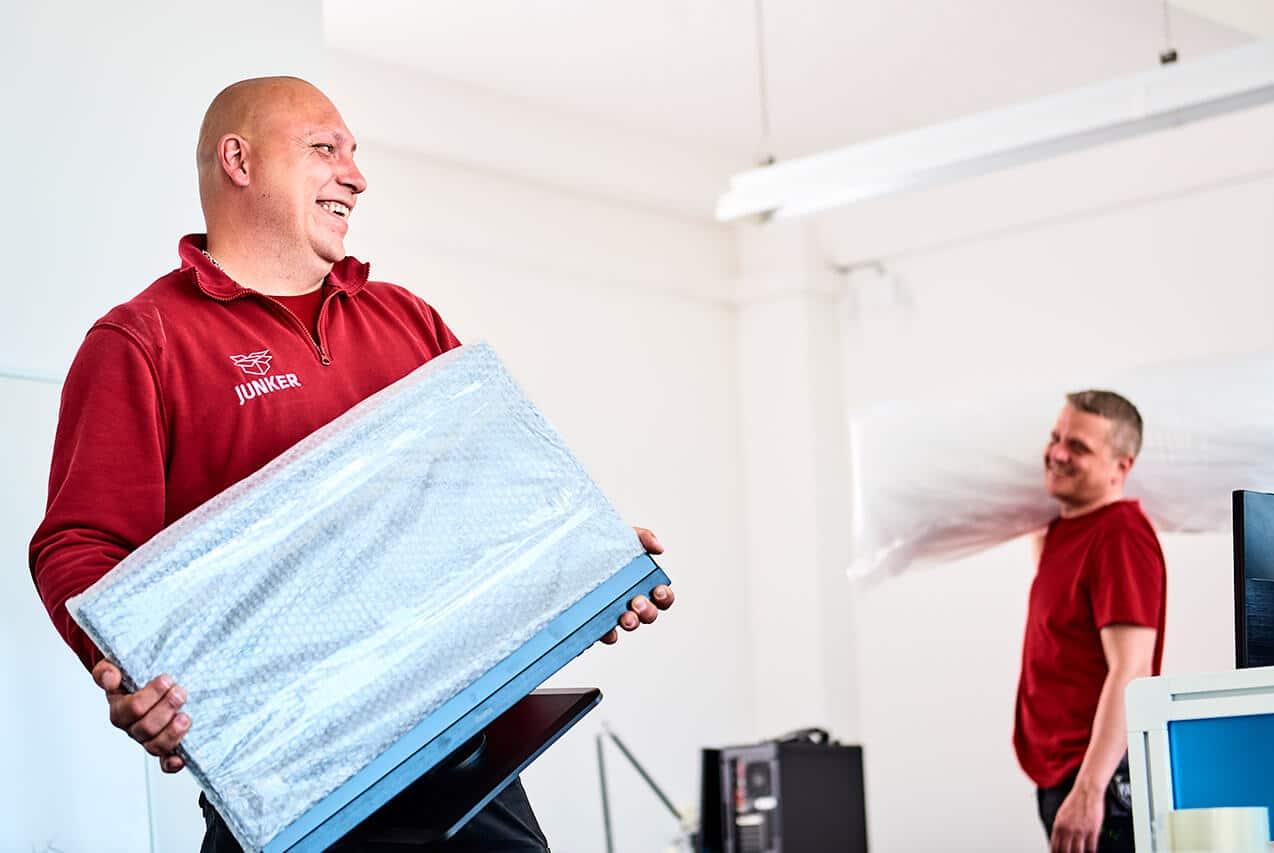 Junker Umzüge Berlin - Büroumzug - Mitarbeiter tragen Büro-Gegenstände