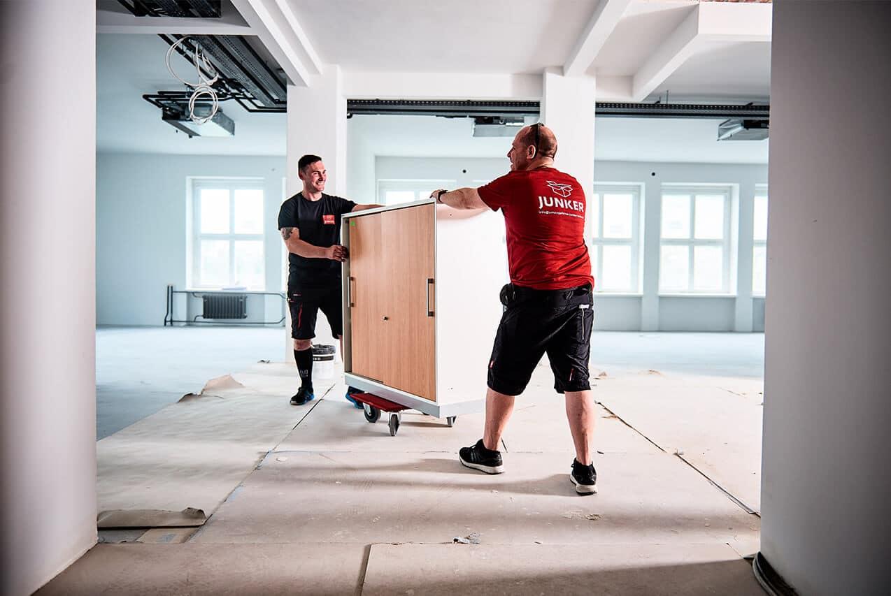 Junker Umzüge Berlin - Büroumzug - Mitarbeiter transportieren Büro-Möbel