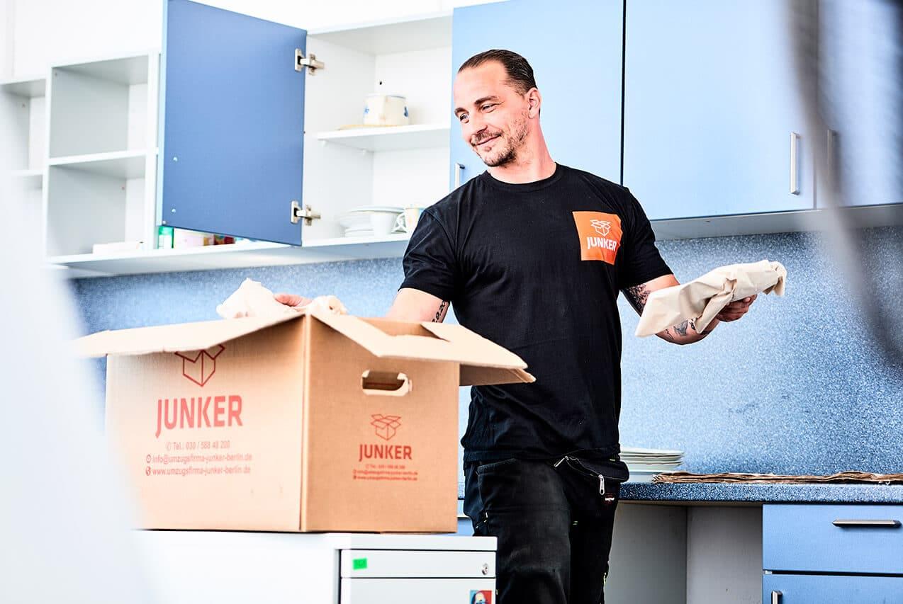 Junker Umzüge Berlin - Wohnungsumzug - Mitarbeiter packt Gegenstände aus dem Umzugskarton aus